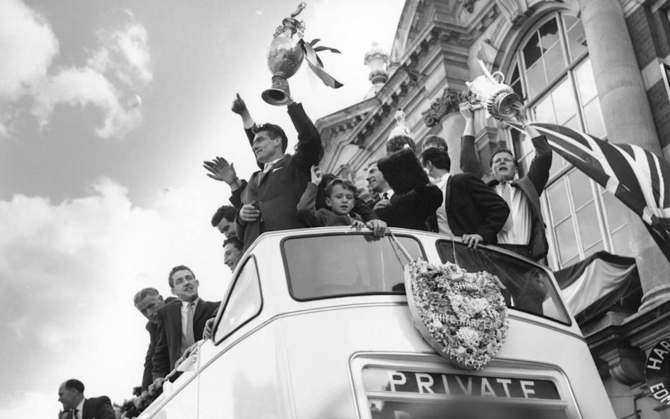 Tottenham Hotspur football club celebrate from the roof of an open top bus on their way to Tottenham Town Hall for a reception given by the Mayor, after winning the League title and the FA Cup 'double' - Fox Photos/Getty Images