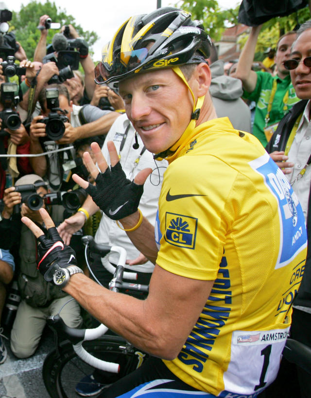FILE - In this July 24, 2005, file photo, overall leader Lance Armstrong, of Austin, Texas, surrounded by press photographers, gestures seven, for his seventh straight win in the Tour de France cycling race, prior to the start of the 21st and final stage of the race, between Corbeil-Essonnes, south of Paris, and the French capital. Armstrong, on Thursday, April 19, 2018, has reached a $5 million settlement with the federal government in a whistleblower lawsuit that could have sought $100 million in damages from the cyclist who was stripped of his record seven Tour de France victories after admitting he used performance-enhancing drugs throughout much of his career. (AP Photo/Peter Dejong, File)