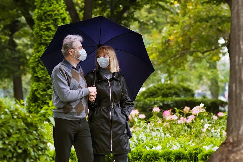 Retired couple walking in a park under quarantine during coronavirus outbreak