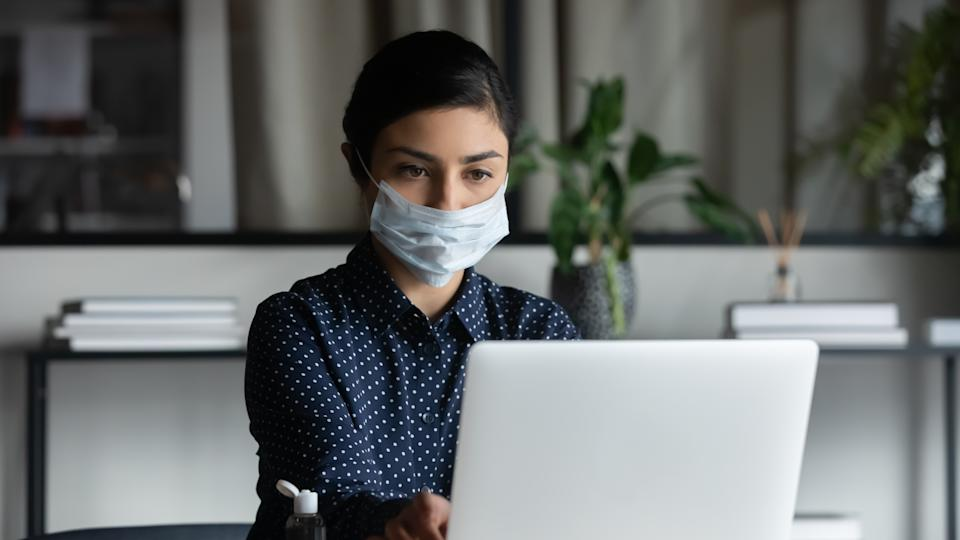 Concentrated young female indian professional wearing breath protective mask, working on computer after washing hands with antiseptic liquid, preventing spreading coronavirus infection in office.Working from home has created a whole new issue around online security. Here's how to protect yourself. (Photo: Getty)