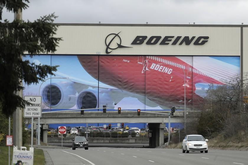 FILE - In this March 23, 2020, file photo, cars are driven near Boeing's manufacturing facility in Everett, Wash., north of Seattle. Boeing says it will resume production of its commercial airplanes in phases at its Seattle area facilities next week after suspending operations in March because of the COVID-19 pandemic. The company says 27,000 of its employees will return to work under new measures put in place to keep people safe and fight the spread of the virus. Employees for the 737, 747, 767 and 777 airplanes will return as early as Monday, April 20, with most returning to work by Tuesday, officials said. (AP Photo/Ted S. Warren, File)