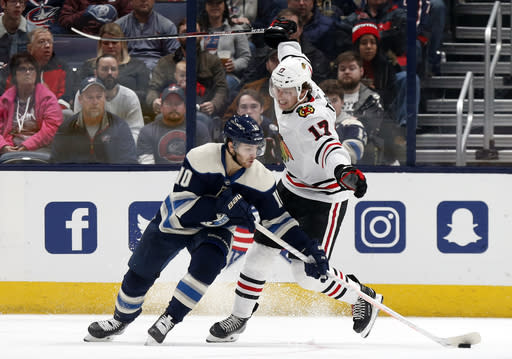 Columbus Blue Jackets forward Alexander Wennberg, left, of Sweden, controls the puck in front of Chicago Blackhawks forward Dylan Strome during the second period of an NHL hockey game in Columbus, Ohio, Sunday, Dec. 29, 2019. (AP Photo/Paul Vernon)