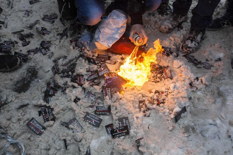 In this photo taken on Friday, March 15, 2013, members of a pro-Kremlin youth group burn plastic bags with spice, a synthetic drug, along with business cards that belong to spice pushers, in Moscow, Russia. Russian officials and anti-drugs campaigners say that spice has become one of the most dangerous drugs widely available to youngsters and almost impossible to ban because of the constantly changing chemical ingredients. (AP Photo/Alexander Zemlianichenko Jr)