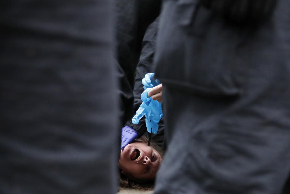 Riot police arrests a protester who shouted 'I can't breathe' after taking part in a 'We Do Not Consent' rally at Trafalgar Square, organised by Stop New Normal, to protest against coronavirus restrictions, in London, Saturday, Sept. 26, 2020. (AP Photo/Frank Augstein)