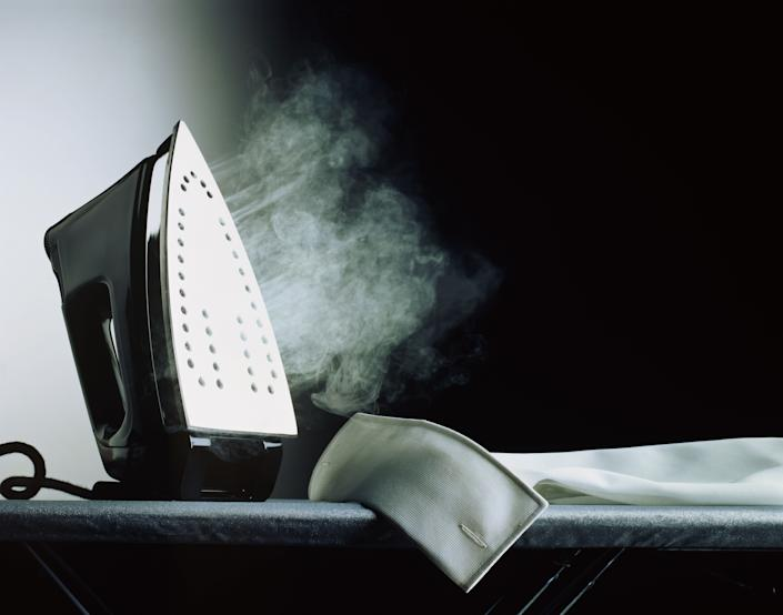 To clean the bottom of the iron, sprinkle salt on the ironing board and iron back and forth.