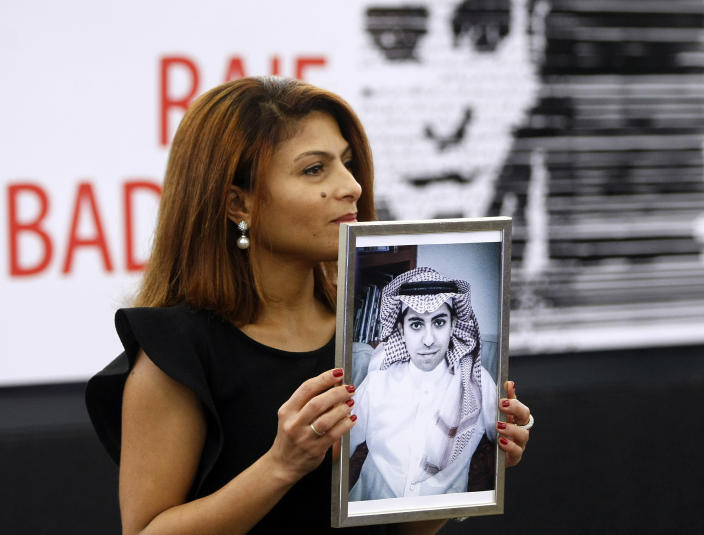 FILE - In this Dec, 16, 2015 file photo, Ensaf Haidar, wife of the jailed Saudi Arabian blogger Raif Badawi, shows a portrait of her husband as he is awarded the Sakharov Prize, in Strasbourg, France. Saudi Arabia's King Salman ordered an end to the death penalty for crimes committed by individuals when they were minors, according to a statement Sunday, April 26, 2020, by a top official. The decision comes on the heels of another which orders judges to end the practice of flogging. Five years ago, the public flogging of Badawi 50 times before hundreds of spectators in the metropolitan city of Jiddah drew outrage and condemnation from around the world. (AP Photo/Christian Lutz, File)