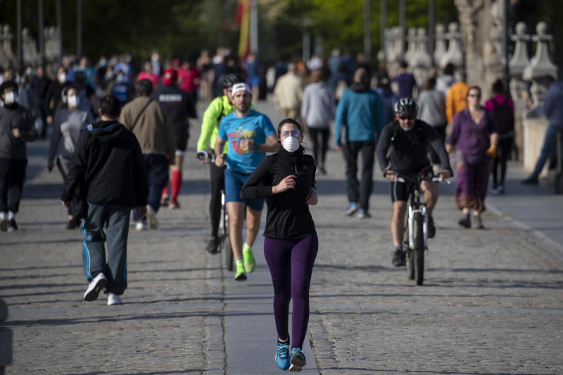 In this photo taken with a telephoto lens, people cross the Toledo bridge in Madrid, Spain, Sunday, May 3, 2020. On Saturday, Spaniards were able to go outdoors to do exercise for the first time in seven weeks since the lockdown began to battle the coronavirus outbreak. (AP Photo/Manu Fernandez)