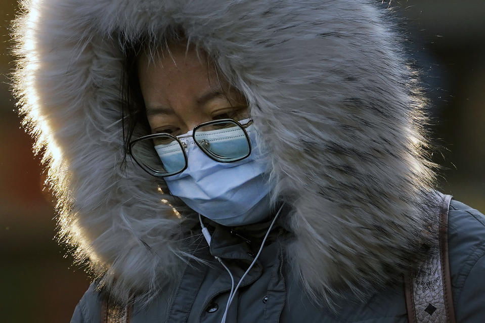 A woman wearing a face mask to help curb the spread of the coronavirus walks on a street in Beijing, Monday, Jan. 4, 2021. Wary of another wave of infections, China is urging tens of millions of migrant workers to stay put during next month's Lunar New Year holiday, usually the world's largest annual human migration. (AP Photo/Andy Wong)