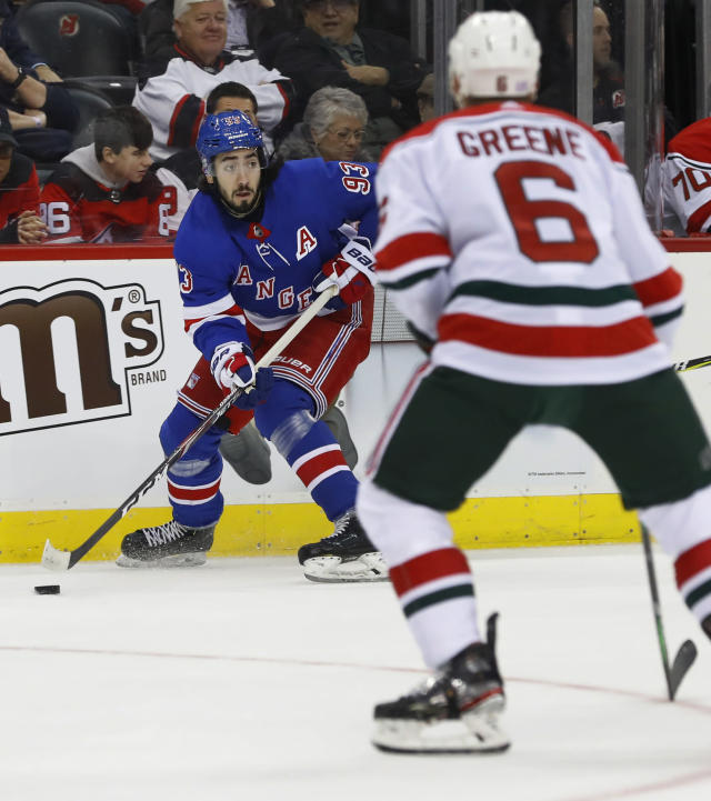 New York Rangers center Mika Zibanejad (93) plays the puck as New Jersey Devils defenseman Andy Greene (6) defend during the first period of an NHL hockey game Saturday, Nov. 30, 2019, in Newark, N.J. (AP Photo/Noah K. Murray)