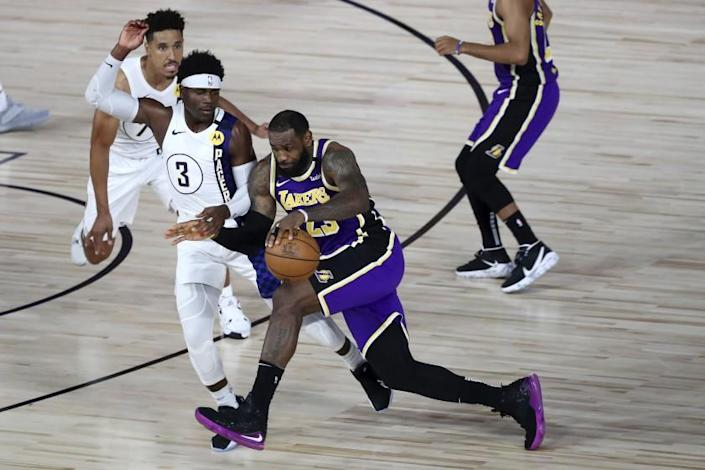 """The Lakers' LeBron James, who finished with 31 points, drives against the Pacers' Aaron Holiday during the fourth quarter Saturday. <span class=""""copyright"""">(Kim Klement / Pool photo via Associated Press)</span>"""