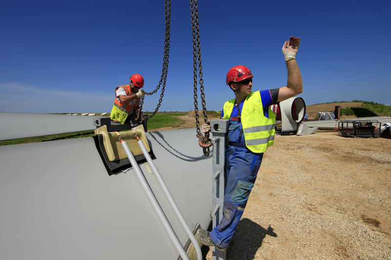 Employees work on a rotor blade of an E-70 wind turbine manufactured by German company Enercon for La Compagnie du Vent (GDF SUEZ Group) during its installation at a wind farm in Meneslies, Picardie region, July 17, 2014. France announced in July a package of tax breaks and low-cost loans to improve insulation in buildings and boost investment in renewable energy, which is supposed to provide 40 percent of the country's electricity by 2030. Picture taken July 17, 2014. REUTERS/Benoit Tessier (FRANCE - Tags: ENERGY BUSINESS CONSTRUCTION ENVIRONMENT)