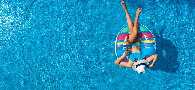 A woman floats on a raft in a swimming pool.