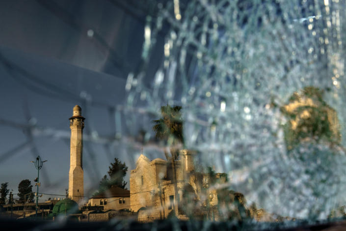 FILE - In this May 26, 2021 file photo, the minaret of the Al-Omari mosque and St. George Greek Orthodox church are reflected in the broken windshield of a vehicle sitting outside a synagogue in the mixed Arab-Jewish town of Lod, central Israel, in the wake of clashes between Arabs, police and Jews. Israeli police said Sunday, June 20, 2021, that they have arrested eight Arab suspects in the killing of Yehoshua during a wave of ethnic violence in May. Yehoshua, 56, died after being pelted with rocks during clashes between Arabs and Jews in Lod. (AP Photo/David Goldman, File)
