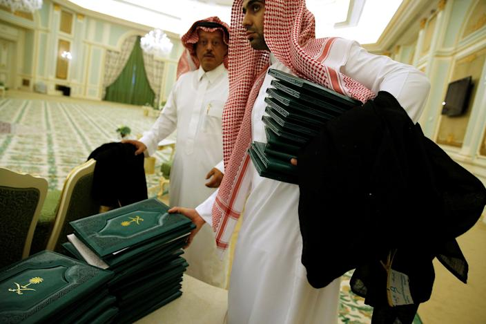 <p>Aides collect folders signifying signed agreements between the Saudi government and U.S. companies after a signing ceremony with Saudi Arabia's King Salman bin Abdulaziz Al Saud and President Donald Trump at the Royal Court in Riyadh, Saudi Arabia on May 20, 2017. (Photo: Jonathan Ernst/Reuters) </p>