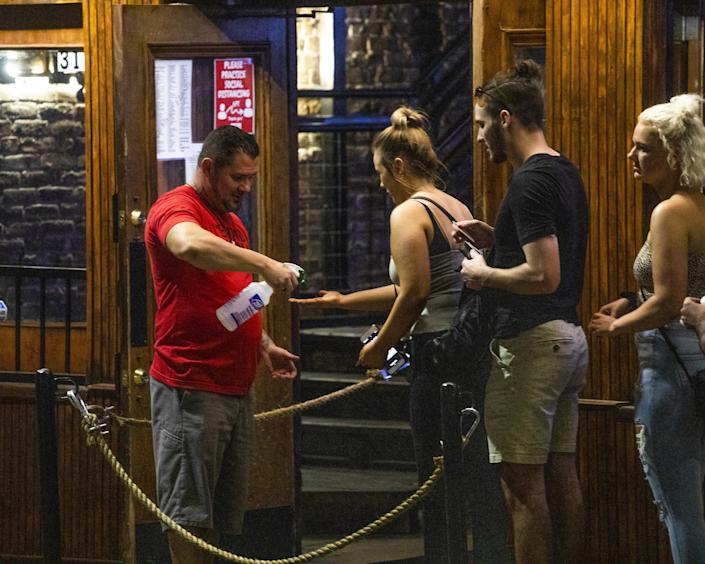 An employee sprays disinfectant on the hands of incoming customers at a bar on Sixth Street at night in downtown Austin, Texas, U.S., on Saturday, May 23, 2020. (Alex Scott/Bloomberg via Getty Images)