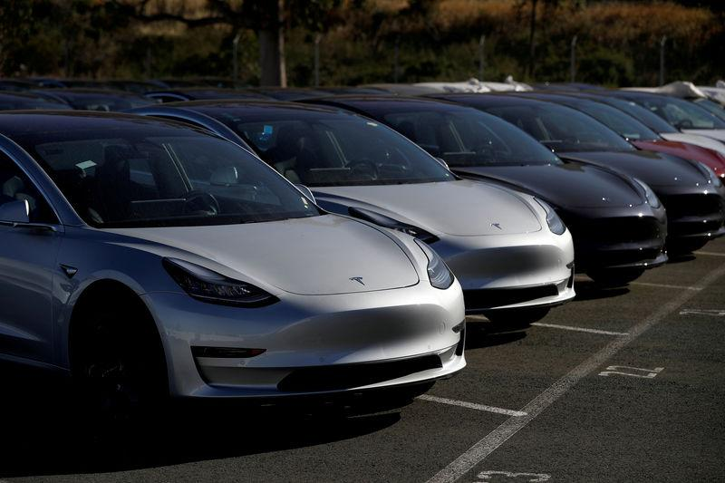 FILE PHOTO: A row of new Tesla Model 3 electric vehicles is seen at a parking lot in Richmond