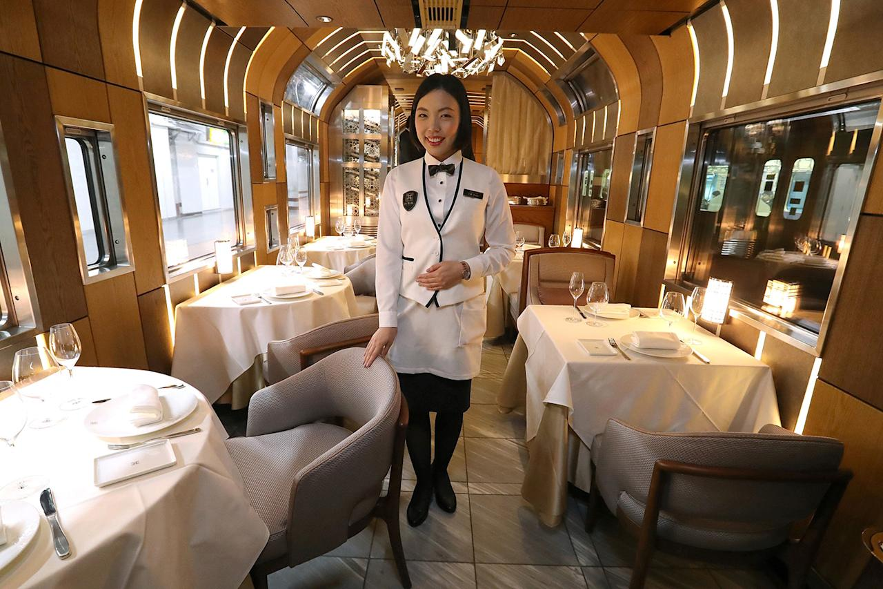 <p>A crew member presents the dining car on East Japan Railway's Train Suite Shiki-shima during a press preview in Tokyo. The10-car, luxury sleeper train includes a lounge and dining car as well as two observatory cars. (Photo: STR/AFP/Getty Images) </p>
