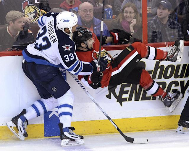 Ottawa Senators' Cory Conacher gets roughed up by Winnipeg Jets' Dustin Byfuglien during the second period of an NHL hockey game in Ottawa, Ontario, on Thursday, Jan. 2, 2014. (AP Photo/The Canadian Press, Sean Kilpatrick)