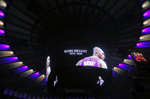 The ceiling of Madison Square Garden is lit in the colors of the Los Angeles Lakers as Kobe Bryant's picture is displayed on a video screen during a moment of silence prior to the start of an NBA basketball game in New York, Sunday, Jan. 26, 2020. Bryant and several others died in a helicopter crash in California Sunday. (AP Photo/Kathy Willens)