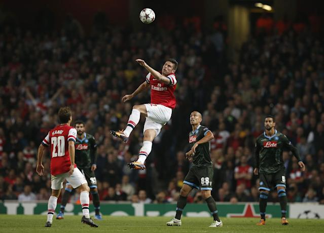 Arsenal's Oliver Giroud, centre, leaps for a header during the Champions League Group F soccer match between Arsenal and Napoli at the Emirates Stadium in London, Tuesday, Oct. 1, 2013. (AP Photo/Matt Dunham)