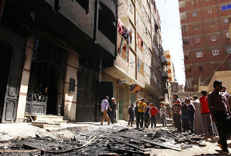 Onlookers gather at the house of Egyptian Christian, Samir Iskandar which was burned during clashes between Muslims and Christians in Qalubiya, just outside Cairo, Egypt, Saturday, April 6, 2013. Several Egyptians including 4 Christians and a Muslim were killed in sectarian clashes before dawn on Saturday, security officials said. (AP Photo/Mohammed Nouhan, El Shorouk Newspaper) EGYPT OUT