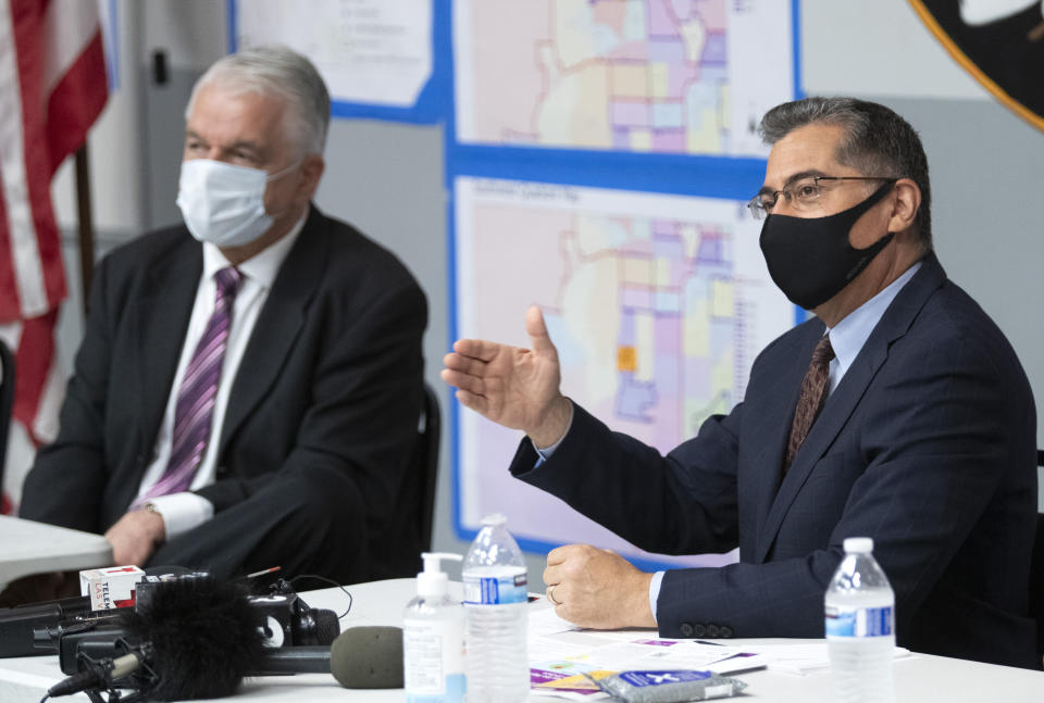 U.S. Department of Health and Human Services (HHS) Secretary Xavier Becerra, right, responds to a question following a briefing from officials at the Clark County Fire Department Training Facility in Las Vegas Thursday, July 22, 2021. Nevada Governor Steve Sisolak listens at left. (Steve Marcus /Las Vegas Sun via AP)