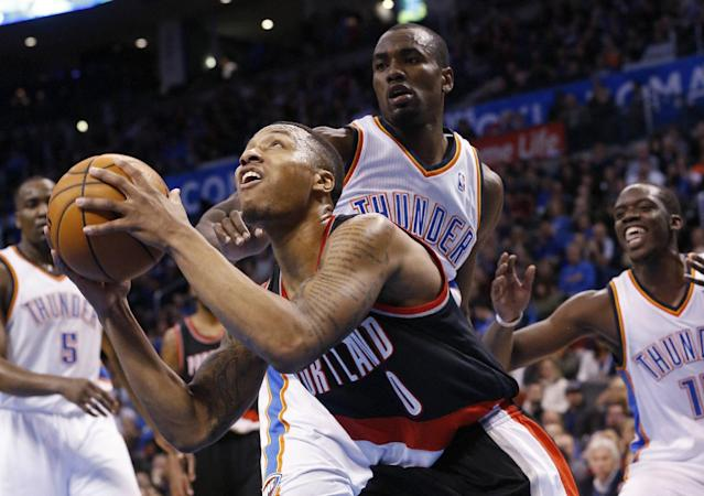 Portland Trail Blazers guard Damian Lillard (0) looks for a shot in front of Oklahoma City Thunder forward Serge Ibaka (9) in the second quarter of an NBA basketball game in Oklahoma City, Tuesday, Jan. 21, 2014. (AP Photo/Sue Ogrocki)