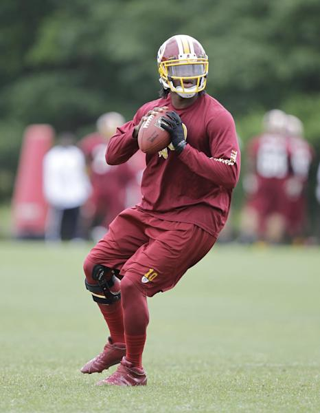 Washington Redskins quarterback Robert Griffin III drops back for a pass during team practice at Redskins Park, Thursday, June 6, 2013, in Ashburn, Va. (AP Photo/Luis M. Alvarez)
