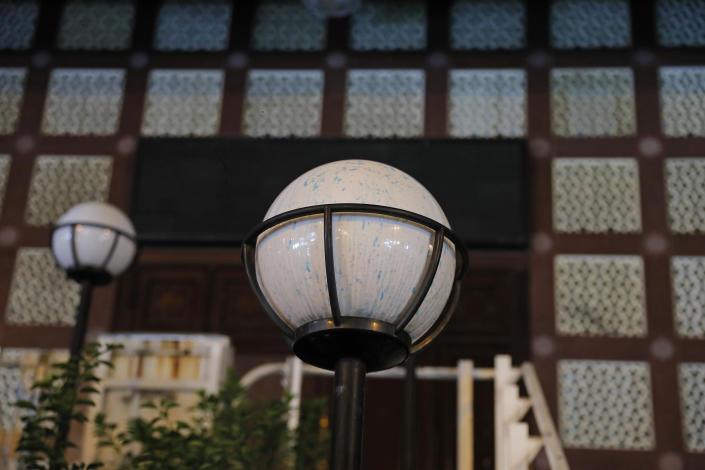 """A lamp outside the mosque is sprayed by blue-dyed liquid in Hong Kong, Sunday, Oct. 20, 2019, after a water cannon truck prayed a stinging blue-dyed liquid as police moved to clear the road of protesters and barricades outside a mosque. Local broadcaster RTHK reported that the people hit were guarding the mosque and few protesters were nearby, and the Hong Kong police force said it was an """"unintended impact"""" of its operation to disperse protesters and later sent a representative to meet the mosque's Imam. (AP Photo/Kin Cheung)"""