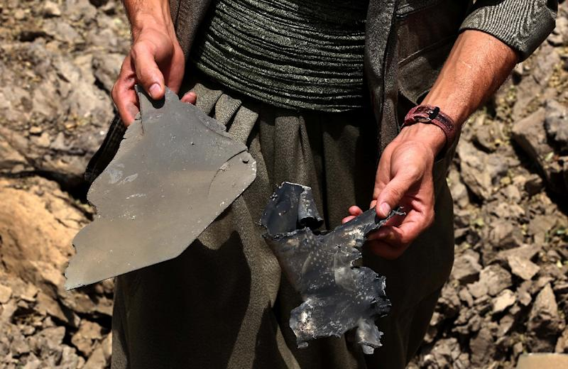 A PKK militant collects pieces of metal as he inspects a crater reportedly caused by a Turkish air strike in the Qandil mountain, the PKK stronghold in northern Iraq, on July 29, 2015