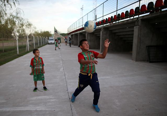 Young supporters of Agropecuario soccer team play outside the Ofelia Rosenzuaig stadium before a match in Carlos Casares, Argentina, April 16, 2018. Picture taken April 16, 2018. REUTERS/Agustin Marcarian