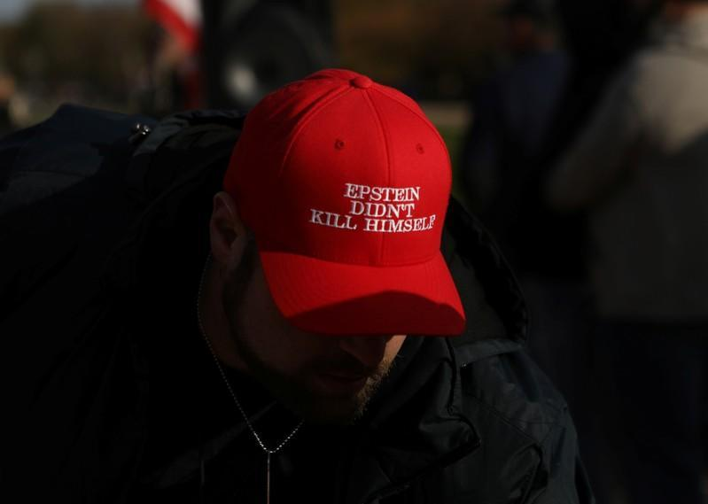 """An attendee wears a hat that says """"Epstein Didn't Kill Himself"""" as militia members and pro-gun rights activists participating in the """"Declaration of Restoration"""" rally listen to speakers in Washington, D.C."""