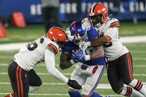 Cleveland Browns' B.J. Goodson, right, and Malcolm Smith, left, tackle New York Giants' Evan Engram, center, during the second half of an NFL football game Sunday, Dec. 20, 2020, in East Rutherford, N.J. (AP Photo/Corey Sipkin)