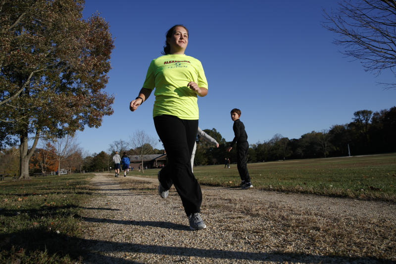 """Grace Brown, 14, poses for a portrait while jogging at the park where she does her jogging workouts for her """"online PE"""" class, in Alexandria, Va., Friday, Nov. 1, 2019. Brown chose to take """"online PE,"""" utilizing a fitness tracker, so that she could take a piano lab as an extra elective. (AP Photo/Jacquelyn Martin)"""