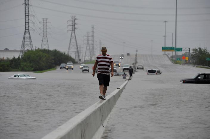 <p>A stranded motorist escapes floodwaters on Interstate 225 after Hurricane Harvey inundated the Texas Gulf coast with rain causing mass flooding, in Houston, Texas, Aug. 27, 2017. (Photo: Nick Oxford/Reuters) </p>