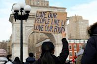 """A woman holds a sign that reads """"Love our people like u love our food"""" at the End The Violence Towards Asians rally in Washington Square Park on February 20, 2021 in New York City"""
