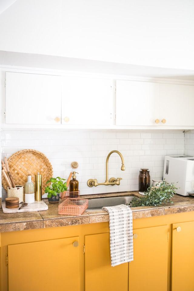 """<p>With the landlord's approval, Elizabeth brushed an unexpected hue on the kitchen cabinets: a golden shade, <a href=""""https://www.sherwin-williams.com/homeowners/color/find-and-explore-colors/paint-colors-by-family/SW6369-tassel#/6369/?"""" target=""""_blank"""">Tassel</a> by Sherwin-Williams. The bold color brightens up the space, yet by leaving the upper cabinets white, the hue doesn't overwhelm the small room. </p> <p>In addition to the paint, geometric brass hardware and white stick-on backsplash tiles help modernize the kitchen. Whether you live in a rental or just want a low-budget way to refresh your kitchen, paint, new hardware, and adhesive tiles can update the space or serve as a temporary fix before you splurge on a complete remodel. </p>"""