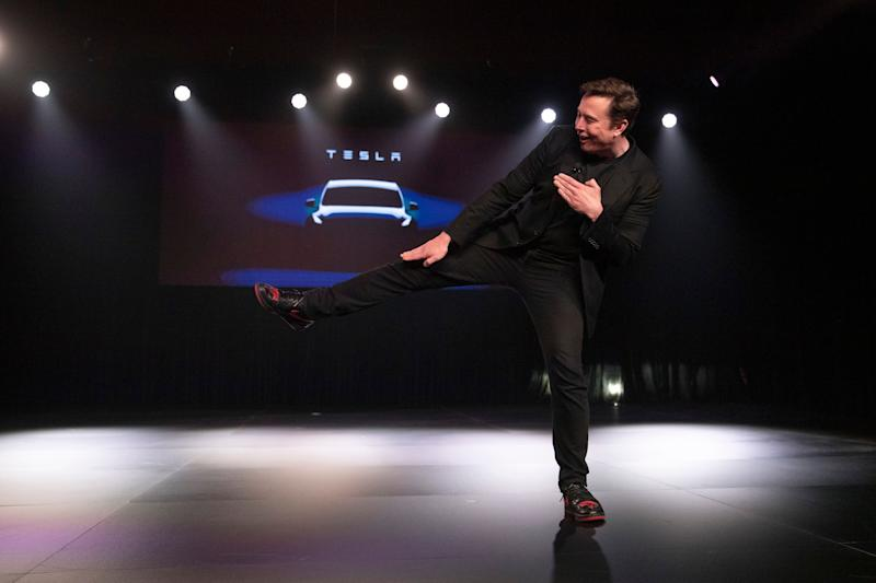 Tesla CEO Elon Musk jokingly motions to kick before introducing the Model Y at Tesla's design studio Thursday, March 14, 2019, in Hawthorne, Calif. The Model Y may be Tesla's most important product yet as it attempts to expand into the mainstream and generate enough cash to repay massive debts that threaten to topple the Palo Alto, Calif., company. (AP Photo/Jae C. Hong)