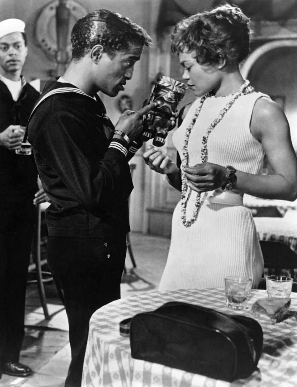 <p>A knit dress complete with a knit belt paired with a long beaded necklace give Kitt a polished look while acting in the film <em>Anna Lucasta</em> with Sammy Davis, Jr. </p>