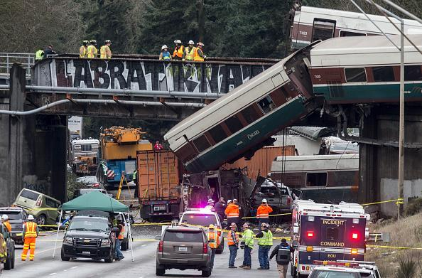 Emergency crews work at the scene of a Amtrak train derailment on December 18, 2017, 2017 in DuPont, Washington. At least six people were killed when a train car plunged from a bridge closing the I-5 southbound. (Photo by Stephen Brashear/Getty Images)