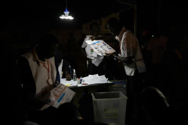 An electoral commission official holds a ballot paper during vote counting at a polling station during Burkina Faso's presidential and legislative elections, on November 22, 2020 in Ouagadougou