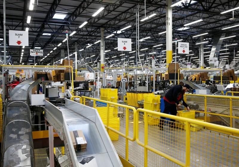 An employee monitors packages at automated scanning and labeling conveyor lines at the Amazon fulfillment center in Kent