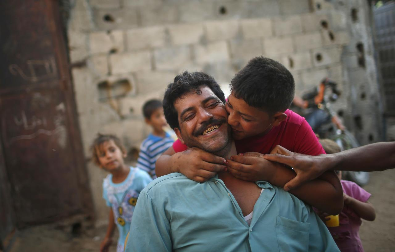 Young Palestinian groom Ahmed Soboh, 15, kisses his bride-to-be's father a day before his wedding to his bride Tala, 14, (not pictured) in the town of Beit Lahiya, near the border between Israeli and northern Gaza Strip September 23, 2013. Picture taken September 23, 2013. REUTERS/Mohammed Salem (GAZA - Tags: SOCIETY CIVIL UNREST)