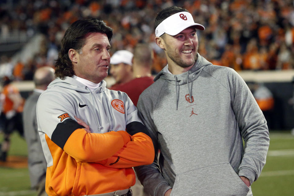 Oklahoma State head coach Mike Gundy, left, talks with Oklahoma head coach Lincoln Riley before their NCAA college football game in Stillwater, Okla., Saturday, Nov. 30, 2019. (AP Photo/Sue Ogrocki)