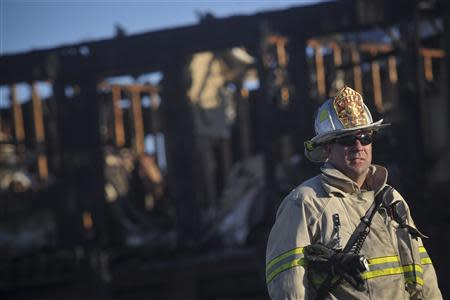 A firefighter stands in front of the charred remains of the Mariner's Cove Inn in Point Pleasant Beach, New Jersey, March 21, 2014. REUTERS/Charles Mostoller