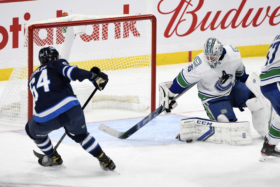 Vancouver Canucks goaltender Thatcher Demko (35) makes a save on Winnipeg Jets' Logan Stanley (64) during the third period of an NHL game in Winnipeg, Manitoba, Monday, May 10, 2021. (Fred Greenslade/The Canadian Press via AP)