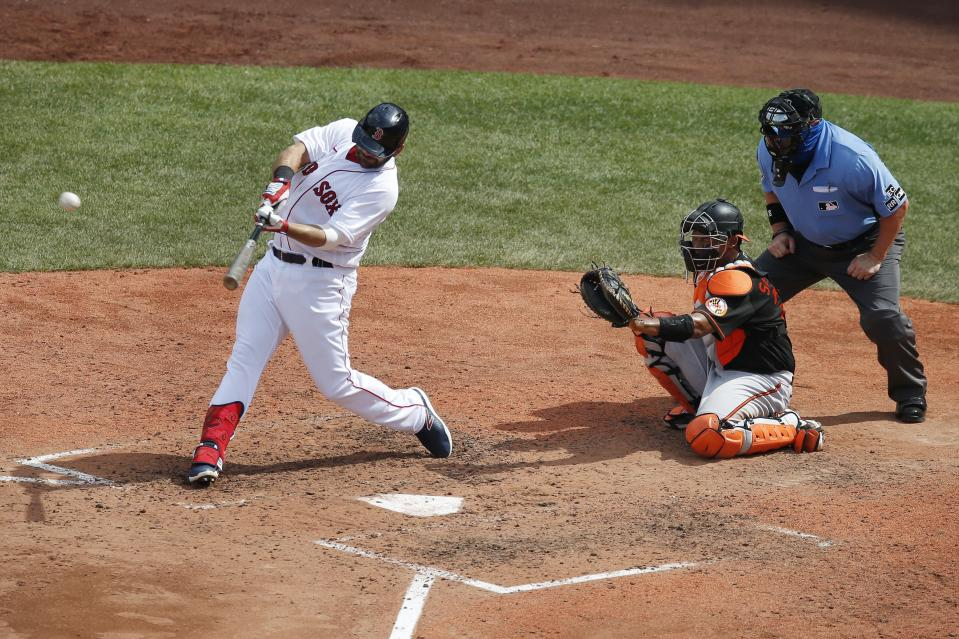Boston Red Sox's Mitch Moreland, left, hits a solo home run in front of Baltimore Orioles' Pedro Severino during the sixth inning of a baseball game Saturday, July 25, 2020, in Boston. (AP Photo/Michael Dwyer)