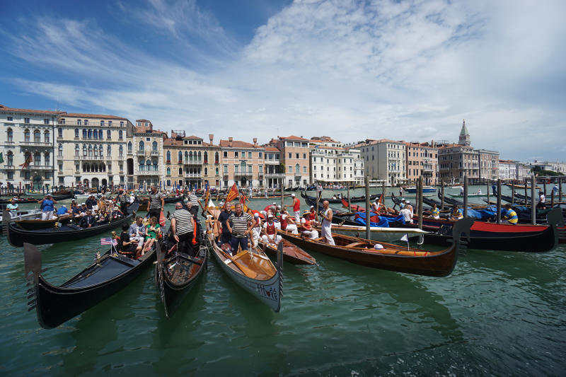 Gondolas are lined up during the Vogada della Rinascita (Rowing of Rebirth) regatta, along Venice canals, Italy, Sunday, June 21, 2020. The regatta was an initiative to pay homage to the medical staff and their hard work and contribution during the COVID-19 pandemic. (Anteo Marinoni/LaPresse via AP)