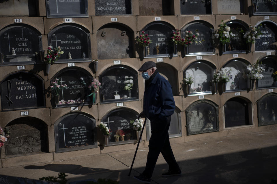 A man wearing face mask protection against COVID-19, walks next to graves decorated with flowers in tribute of deceased relatives at the cemetery during All Saints Day, a Catholic holiday to reflect on the saints and deceased relatives, in Barcelona, Spain, Sunday, Nov. 1, 2020, while Spain suffer a second strong pandemic crisis by Coronavirus. (AP Photo/Emilio Morenatti)