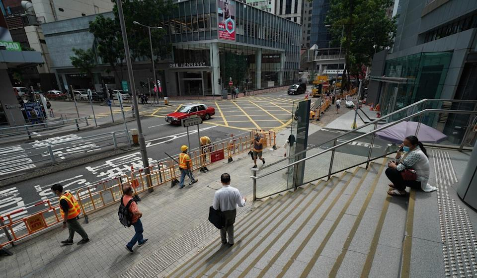 Pedestrians pass in front of police headquarters in Wan Chai after the water-filled barricades there were removed on Sunday. Photo: Felix Wong
